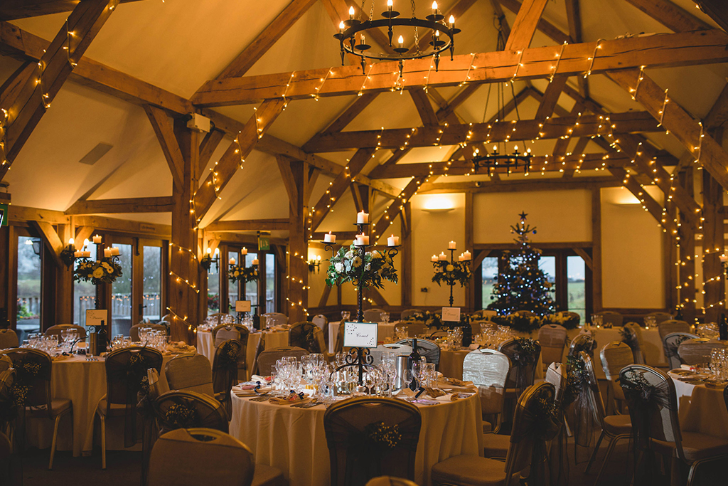 The oak barn was decorated with twinkly fairy lights and a Christmas tree at this festive winter wedding at Sandhole Oak Barn