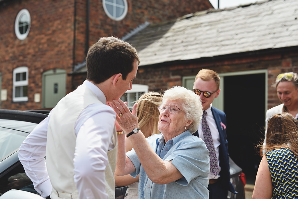 A family member shares some wise words with the groom before the wedding ceremony at Sandhole Oak Barn