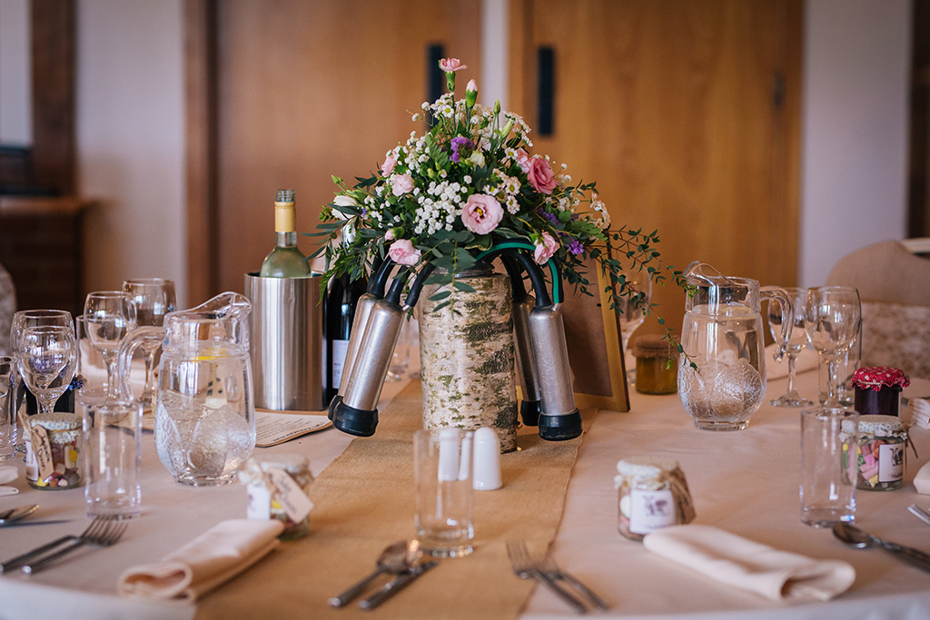 The couple chose quirky table decorations with dairy farming accessories and vases of pretty flowers as table centrepieces at Sandhole Oak Barn