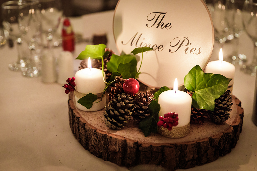 Festive items like candles, ivy and berries displayed on wood slices make perfect winter wedding table centrepieces at Sandhole Oak Barn