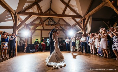 The happy newlyweds take to the floor for their first dance as their guests watch on at this wedding barn in Cheshire