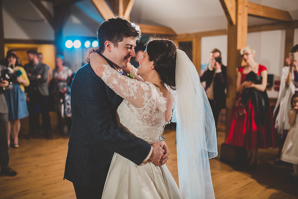 The happy couple have their first dance as their guests watch on at this barn wedding in Cheshire