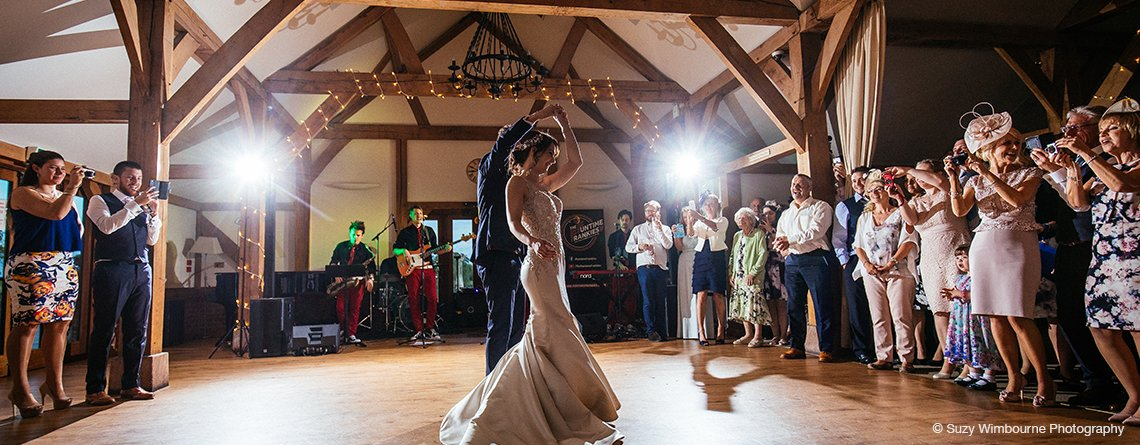 The happy newlyweds take to the dancefloor for their first dance at their wedding reception at Sandhole Oak Barn in the North West