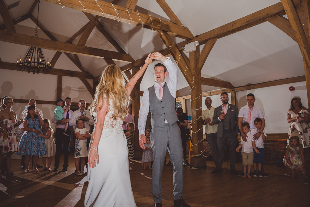 The newlyweds take to the floor for the first dance as their wedding guests look on at Sandhole Oak Barn