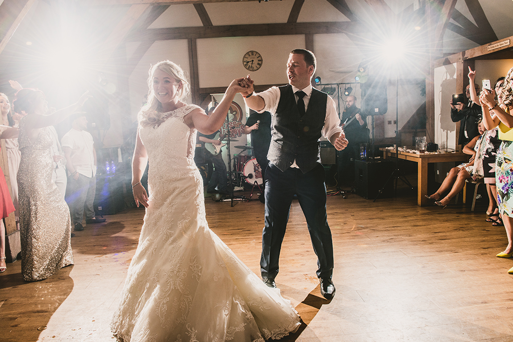 The excited bride and groom enjoy their first dance as Mr and Mrs in front of family and friends