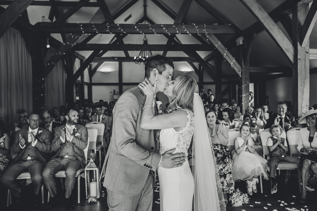 The happy newlyweds have their first kiss at their wedding ceremony at Sandhole Oak Barn