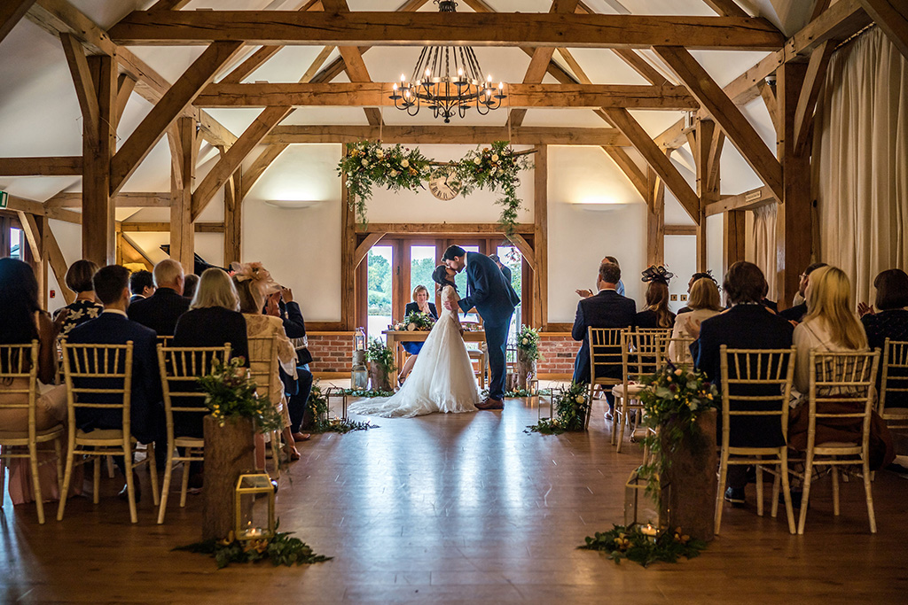 The bride and groom share their first kiss as a married couple at this barn wedding in Cheshire