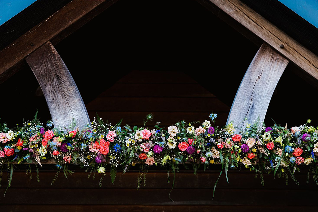 The doorway to the barn was decorated with a beautiful colourful summer flower garland at this barn wedding near Manchester