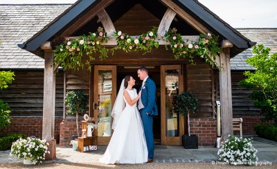 The entrance to the Oak Barn was decorated with garlands of pretty flowers and foliage at this wedding barn in the North West