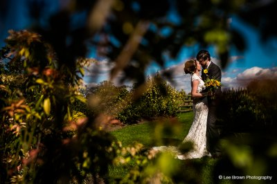 The bride and groom pose for a photo in the beautiful gardens at this summer barn wedding venue near Manchester