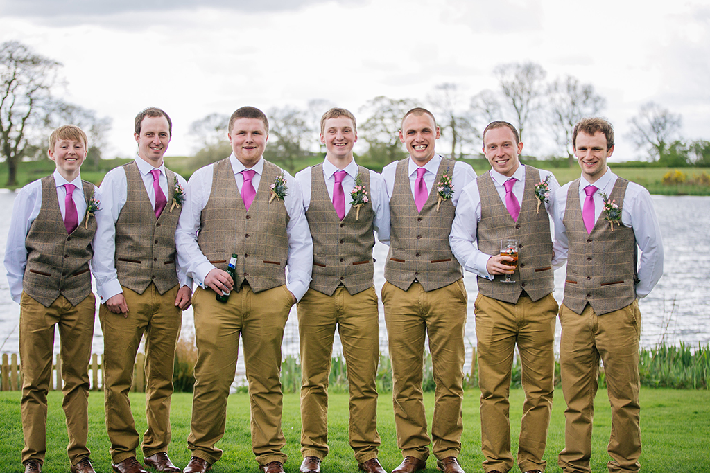 The groom and groomsmen wore country check waistcoats with beige trousers and pink ties at this rustic wedding at Sandhole Oak Barn
