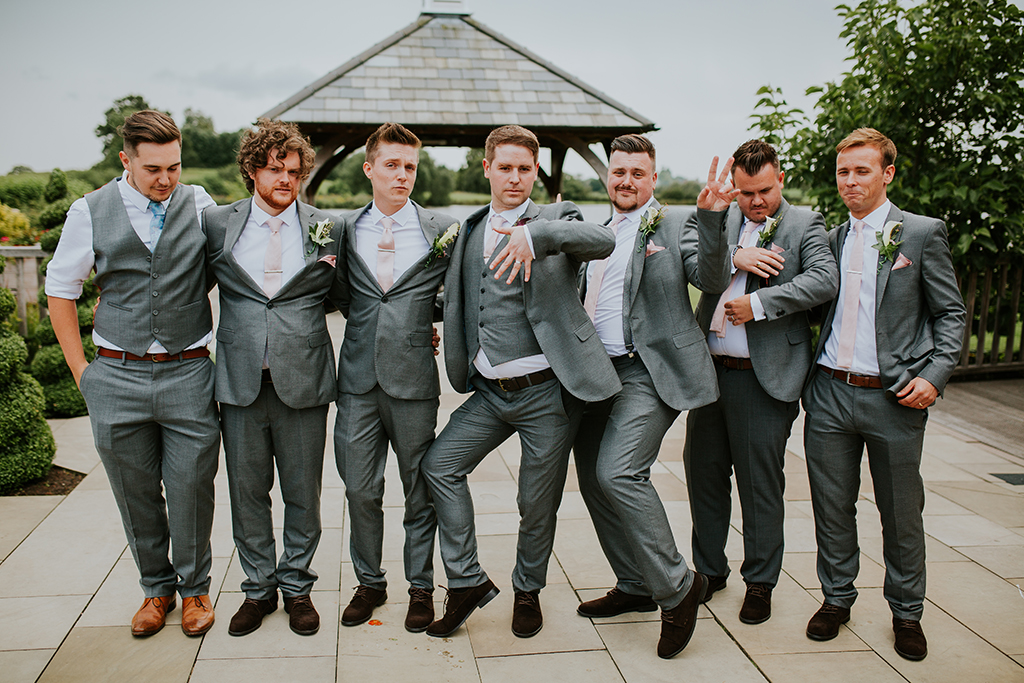 The groom and his groomsmen all wore grey suits with the groomsmen wearing light pink ties