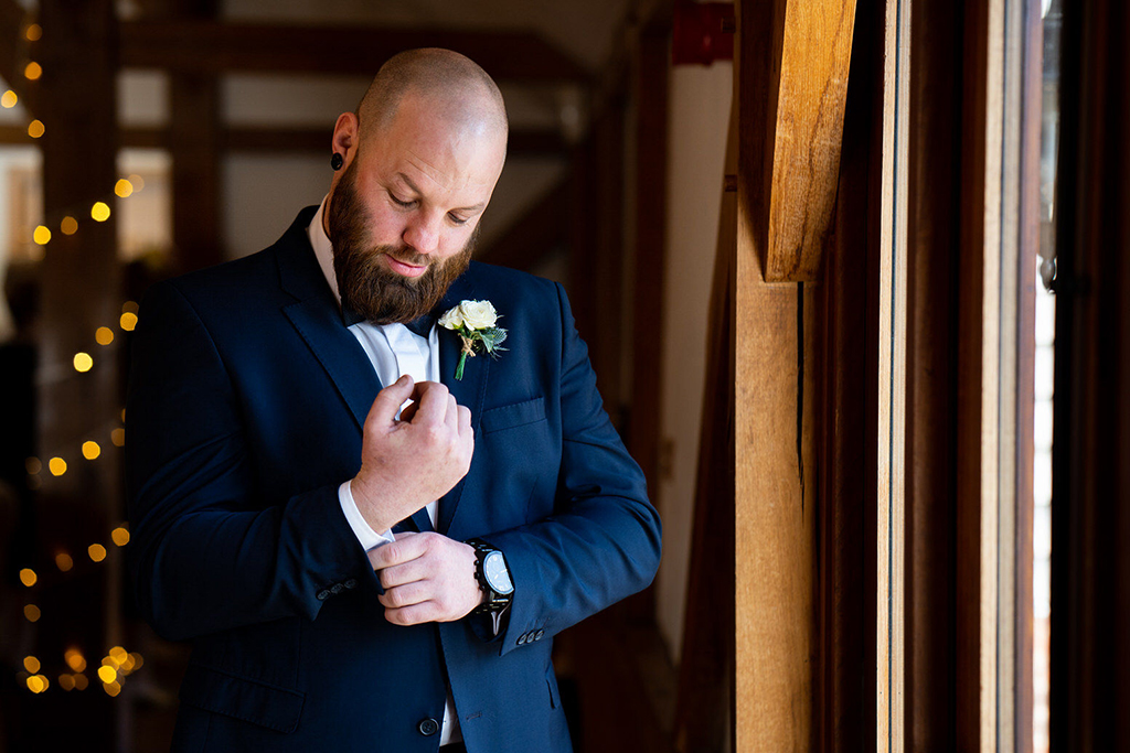 The groom makes the final touches to his outfit before the wedding ceremony at Sandhole Oak Barn