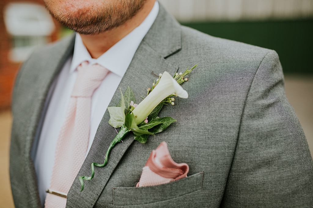 The groom wore a light grey suit with pink handkerchief and floral buttonhole