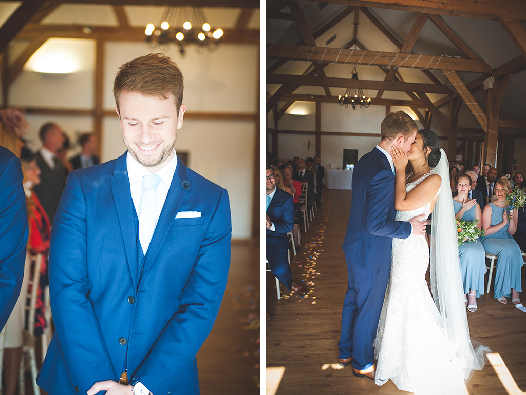 The groom wearing a royal blue suit and pastel blue tie kisses his wife at their wedding ceremony at Sandhole Oak Barn near Manchester.
