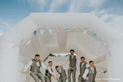 The groomsmen have fun on the bouncy castle at this exclusive use wedding venue