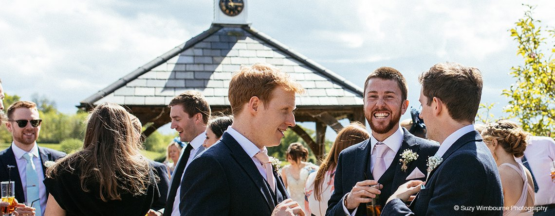 The groomsmen enjoy a funny moment at the drinks reception of this barn wedding at Sandhole Oak Barn Cheshire