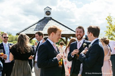 The groomsmen wearing navy suits and pink ties enjoying the outdoor drinks reception at Sandhole Oak Barn near Manchester