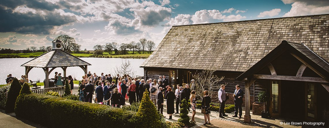 The wedding guests enjoy mingling outside with views of the Clock Tower and lake at this exclusive wedding venue in Staffordshire
