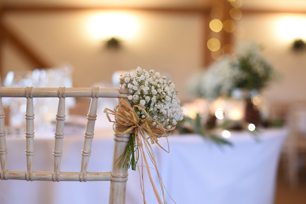 Mini bunches of gypsophila were tied to the chairs at this barn wedding in Cheshire