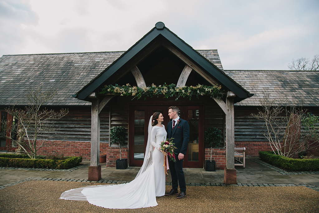 The stunning bride and her groom pose for a photo at the entrance to this rustic barn venue in Cheshire
