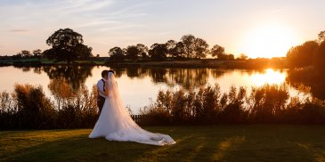 The bride and groom pose for a wedding photo in front of the lake at Sandhole Oak Barn