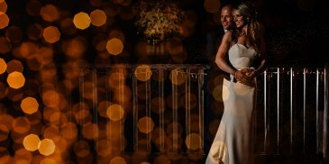 The happy couple pose for an evening wedding photo on the verandah at Sandhole Oak Barn