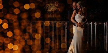 The happy couple pose for an evening wedding photo on the verandah at Sandhole Oak Barn