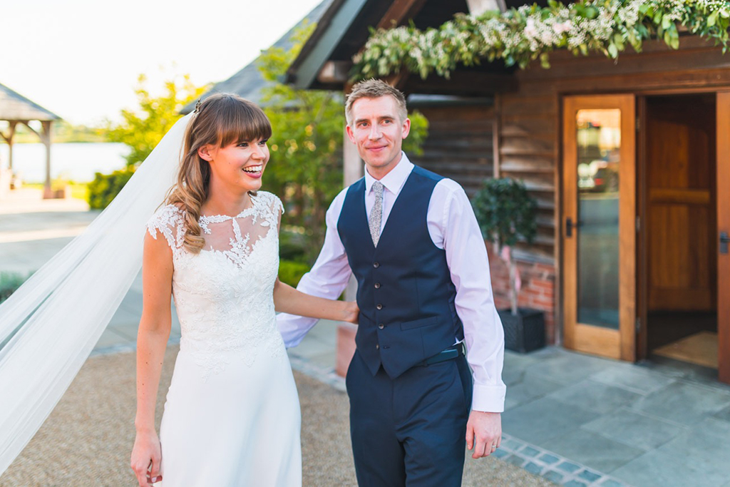 The bride wears an elegant wedding dress with a lace top and the groom wears a navy 3-piece wedding suit at Sandhole Oak Barn