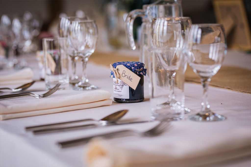 Small jars of homemade jam were given as wedding favours at this rustic barn wedding in Cheshire