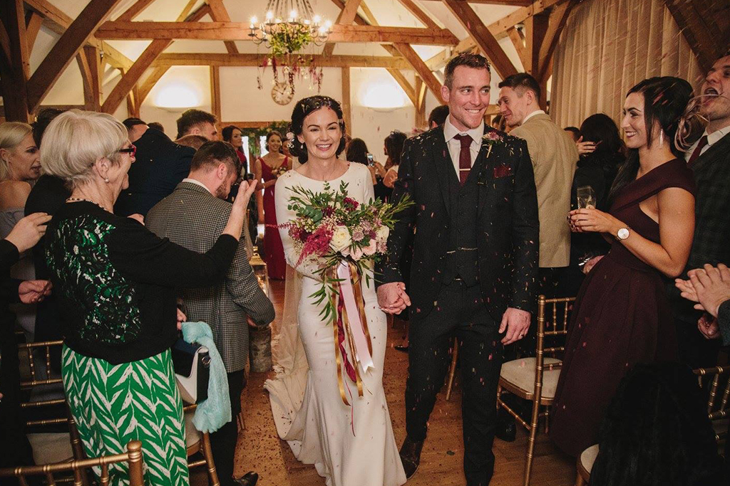 The bride and groom have natural confetti thrown over them after their wedding ceremony at Sandhole Oak Barn in the North West