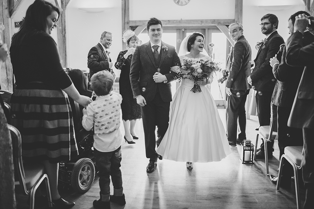 The happy couple walk back down the aisle following their wedding ceremony at Sandhole Oak Barn