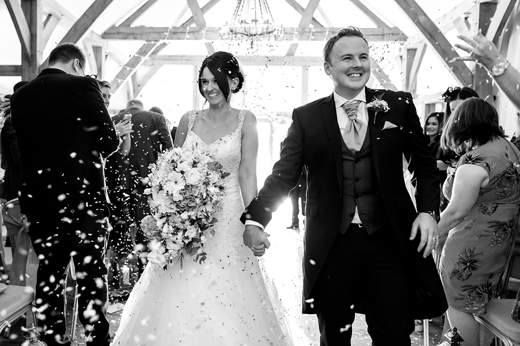The happy newlyweds walk back down the aisle as their guests throw confetti at this wedding at Sandhole Oak Barn in the North West