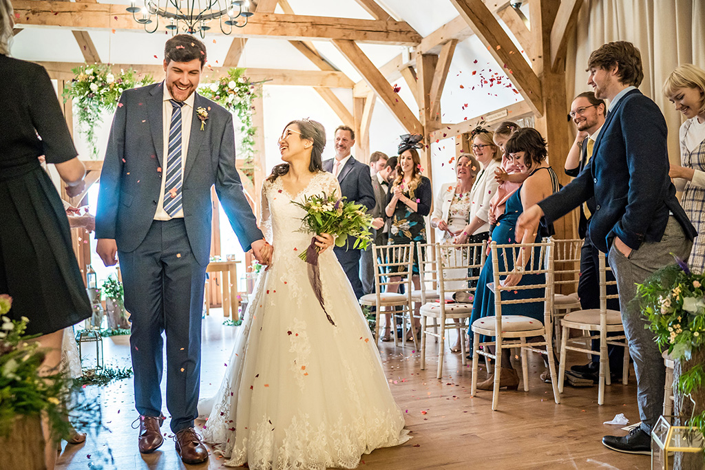 The happy newlyweds have confetti thrown over them as they walk back down the aisle as husband and wife at Sandhole Oak Barn