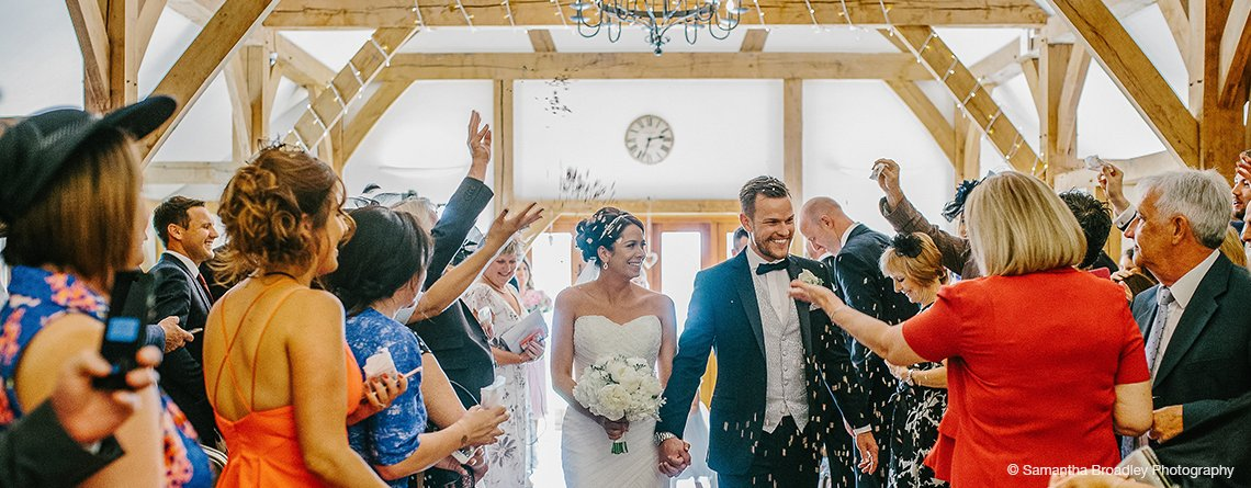 The happy couple have natural petal confetti thrown over them after their wedding ceremony at this barn wedding near Manchester