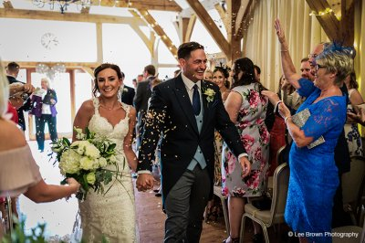The bride and groom have confetti thrown over them after their wedding ceremony at Sandhole Oak Barn near Manchester
