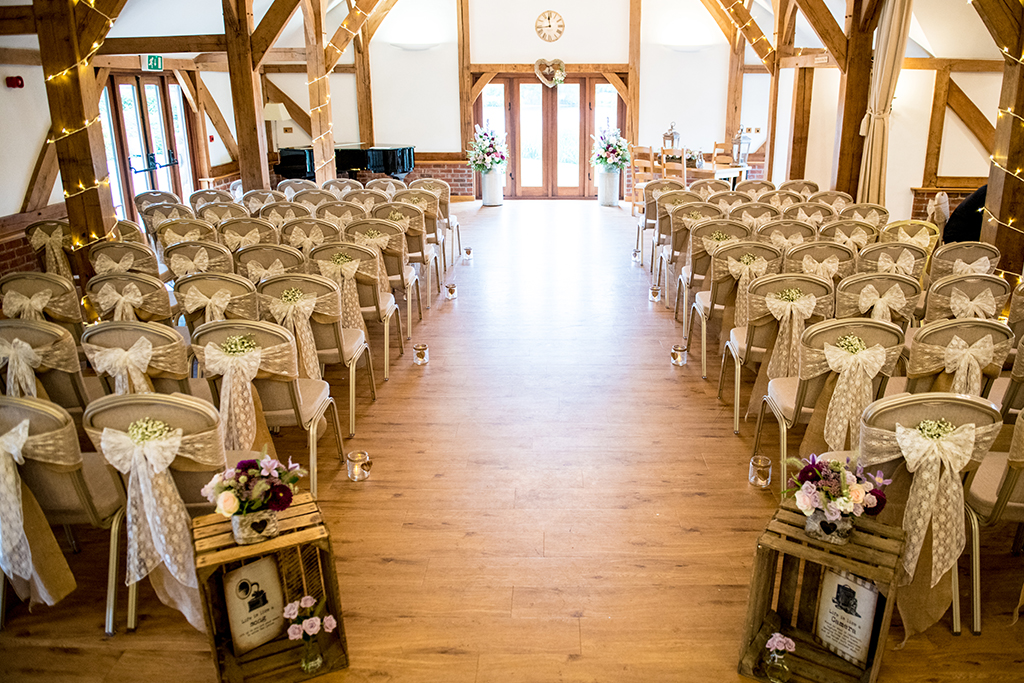 The Oak Barn looks beautiful set up for the wedding ceremony with the chairs decorated with pretty lace and hessian sashes
