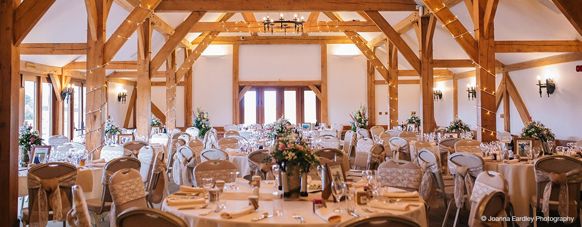 The oak beams were adorned with fairy lights and the chairs were decorated with pretty lace sashes at this wedding reception in Cheshire