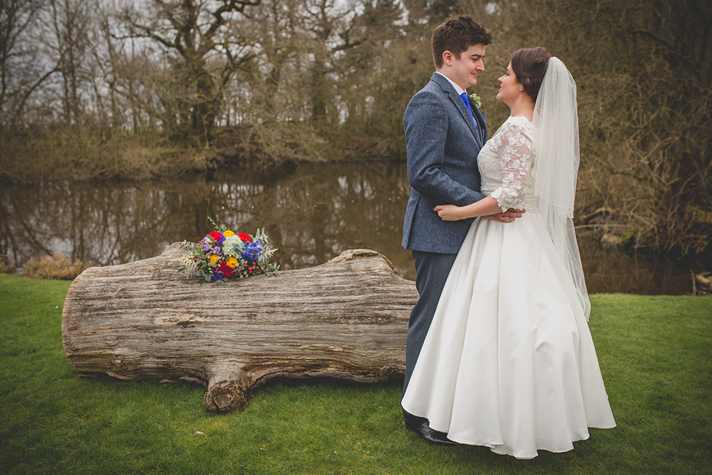 The happy newlyweds pose for a photo by the lake at this rural wedding venue in Cheshire