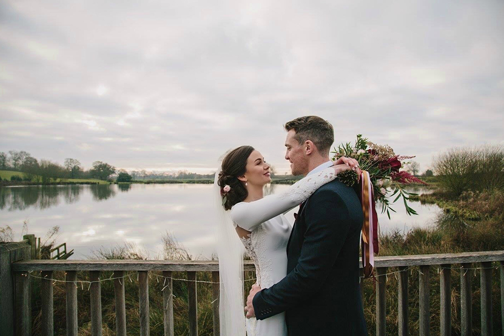 The happy couple pose for a photo by the lake at this rural wedding venue in Cheshire