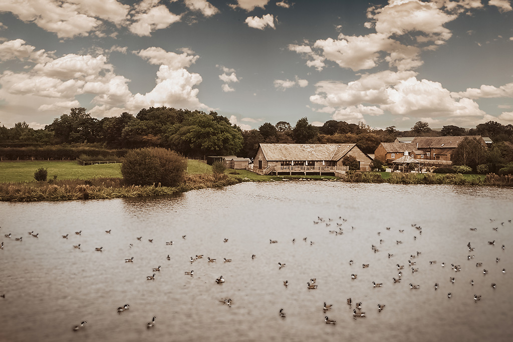 A beautiful view over the lake at rural wedding venue Sandhole Oak Barn in Cheshire