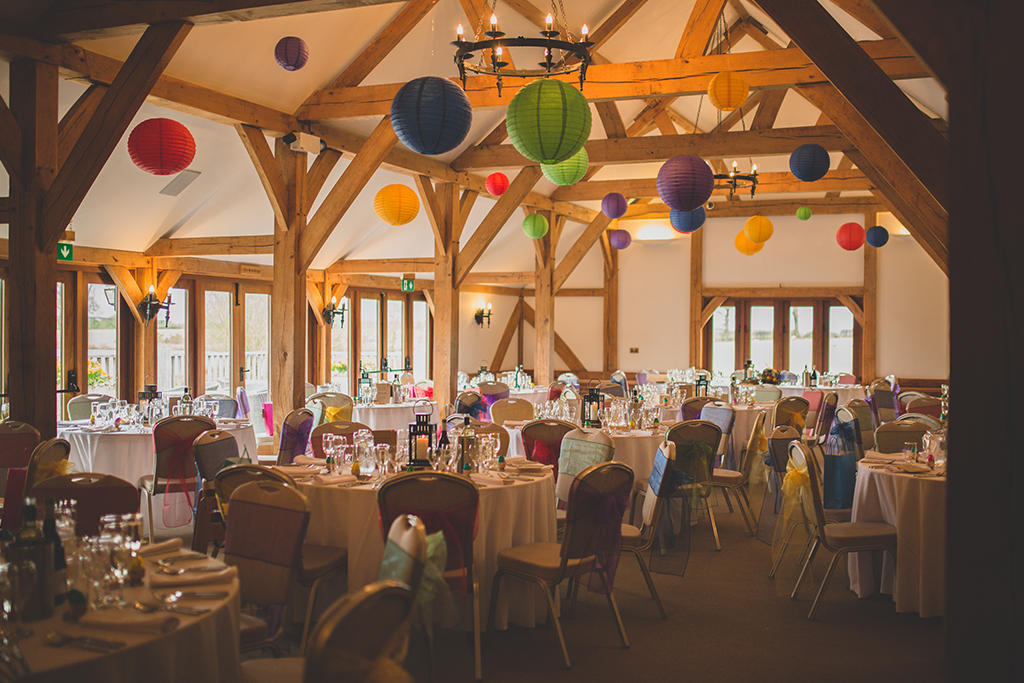 The barn was decorated with colourful lanterns and sashes at this spring wedding at Sandhole Oak Barn in Cheshire