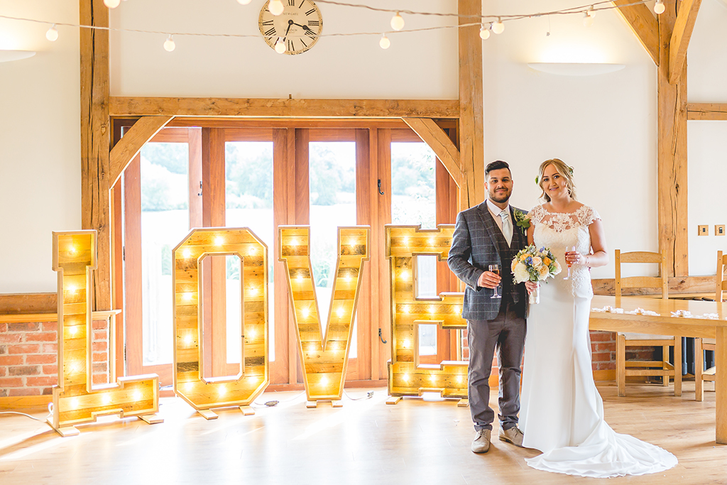The happy newlyweds pose for a wedding photo by the love letter lights at this summer wedding at Sandhole Oak Barn
