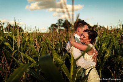 The happy newlyweds pose for a photo in the maize fields at this rural wedding venue near Manchester
