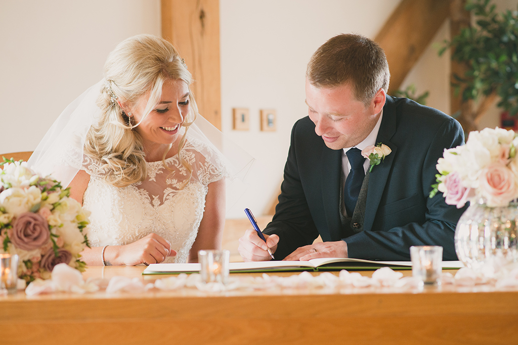 The happy newlyweds sign the register together inside the stunning barn wedding venue