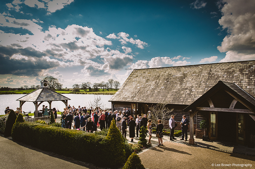 Wedding guests at Sandhole Oak Barn in Cheshire enjoy an outdoor drinks reception following the wedding ceremony