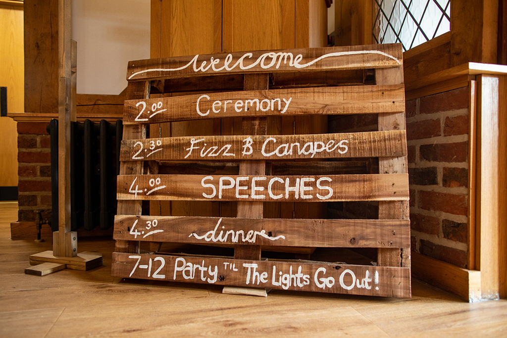 A wooden wedding sign was used for the order of the day at his rustic wedding venue in Cheshire