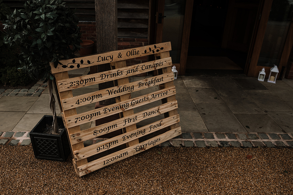 The couple displayed their order of the day on a wooden pallet sign at their rustic wedding at Sandhole Oak Barn