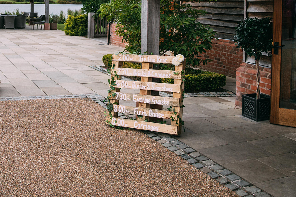 Using pallets to display your order of the day work well with a rustic autumn wedding theme