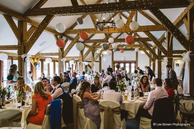 The barn was decorated with grey and orange paper lanterns at this barn wedding in Cheshire
